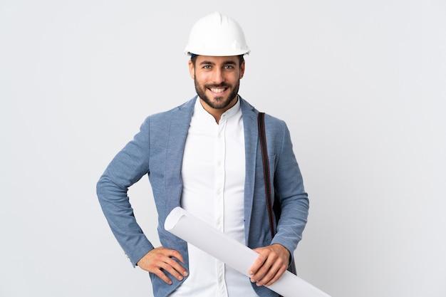 Jovem arquiteto com capacete e segurando plantas isoladas na parede branca, posando com os braços na cintura e sorrindo