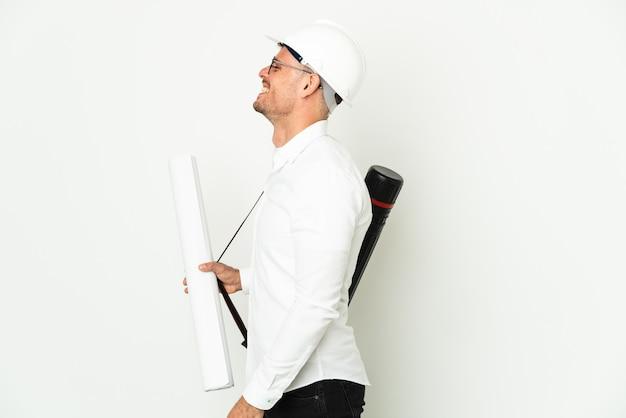 Jovem arquiteto com capacete e segurando plantas isoladas no fundo branco rindo em posição lateral