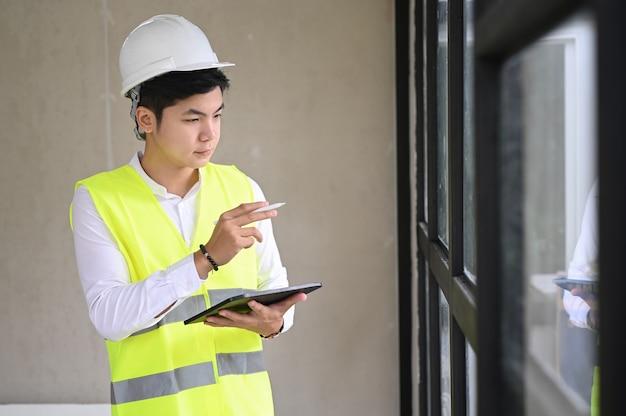 Jovem arquiteto com capacete e tablet no canteiro de obras, conceito de lista de verificação