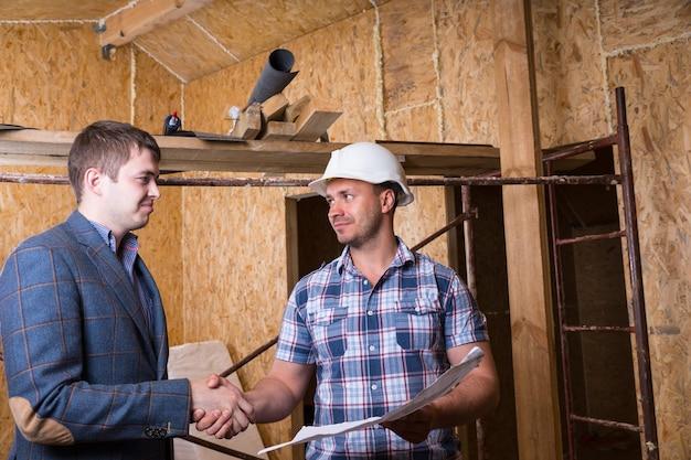 Jovem arquiteto e capataz da construção civil com planos de construção apertando as mãos dentro de uma casa inacabada com placas de madeira compensada de partículas expostas