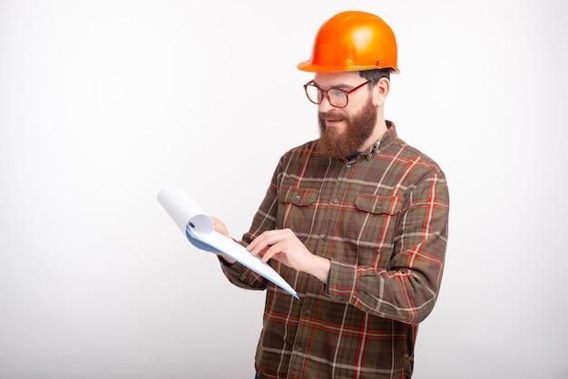Jovem arquiteto está olhando através de planos e documentos, usando capacete laranja e espaço em branco.