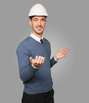 Jovem arquiteto fazendo gesto de boas-vindas com a mão