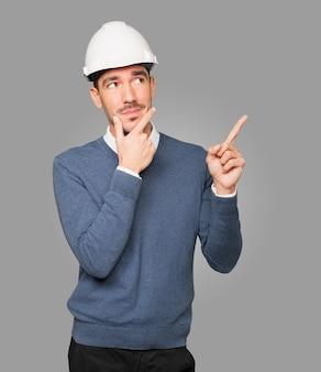 Jovem arquiteto fazendo um gesto de dúvida e apontando com o dedo