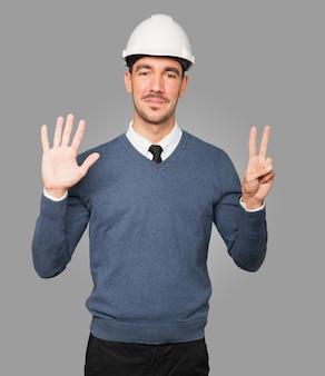 Jovem arquiteto fazendo um gesto de número sete