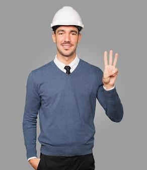 Jovem arquiteto fazendo um gesto de número três