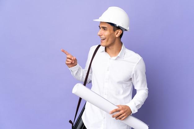Jovem arquiteto isolado apontando o dedo para o lado e apresentando um produto