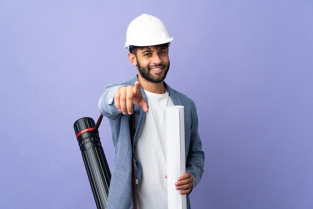 Jovem arquiteto marroquino com capacete e segurando plantas na parede isolada apontando para a frente com uma expressão feliz