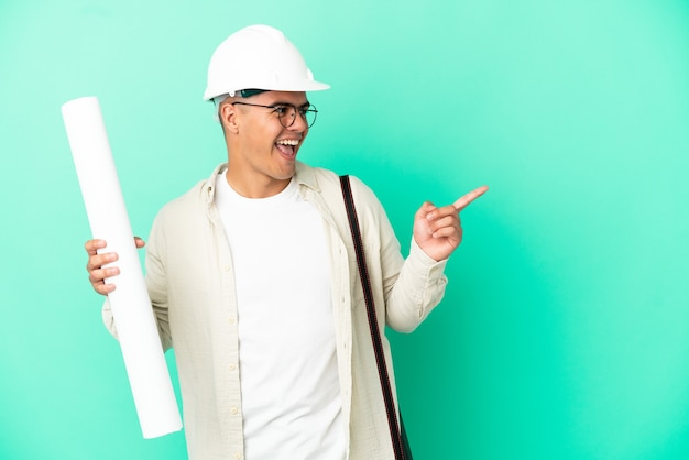 Jovem arquiteto segurando plantas sobre um fundo isolado, apontando o dedo para o lado e apresentando um produto
