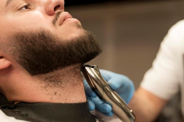 Jovem arrumando a barba no barbeiro