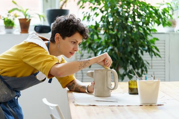 Jovem artesã ocupada com a modelagem de jarro de argila crua durante uma aula de cerâmica ou oficina em estúdio