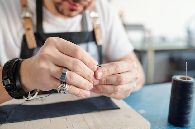 Jovem artesão colocando linha preta no orifício da agulha sobre uma placa de madeira com um pedaço de couro antes de costurar