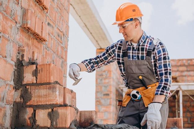 Jovem artesão construindo uma casa