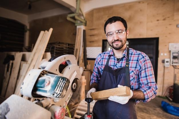Jovem artesão de uniforme trabalhando na carpintaria
