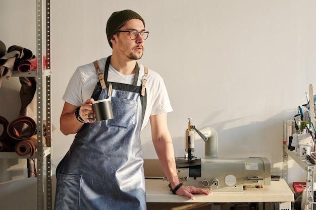 Jovem artesão tranquilo com avental de couro e chapéu de gorro segurando uma caneca com uma bebida enquanto está de pé ao lado da mesa na oficina