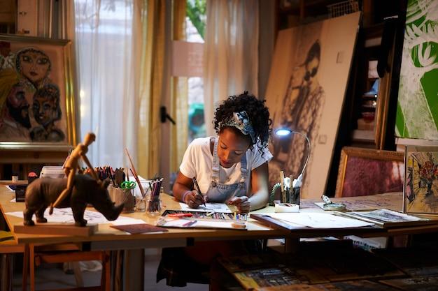 Jovem artista afro-americana trabalhando no estúdio, pessoa criativa fazendo arte