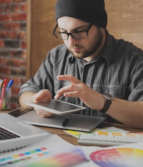 Jovem artista criativa de web design no chapéu com tablet gráfico no escritório moderno apartamento