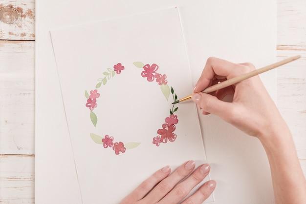 Jovem artista desenho padrão de flores com tinta aquarela e pincel no local de trabalho