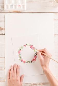 Jovem artista desenho padrão de flores com tinta aquarela e pincel no papel no local de trabalho