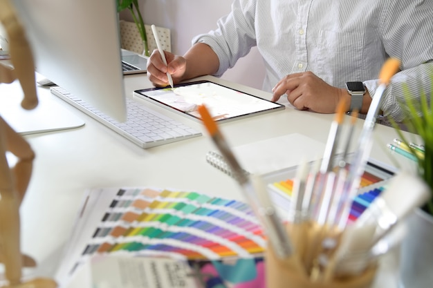 Jovem artista e designer gráfico no espaço de trabalho de estúdio