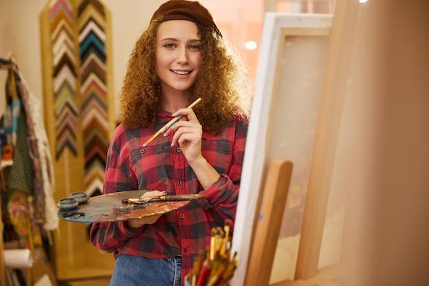 Jovem artista encaracolada parece feliz e segura uma paleta com tintas a óleo