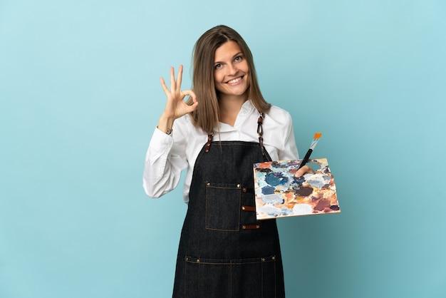 Jovem artista eslovaca isolada em fundo azul mostrando sinal de ok com os dedos