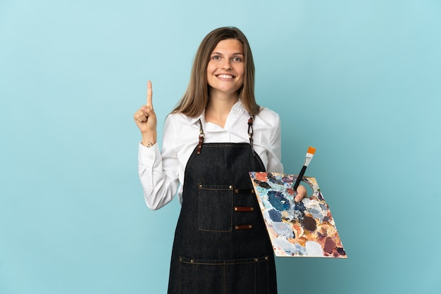 Jovem artista eslovaca isolada em um fundo azul apontando uma ótima ideia