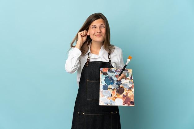 Jovem artista eslovaca isolada em um fundo azul frustrada e cobrindo as orelhas