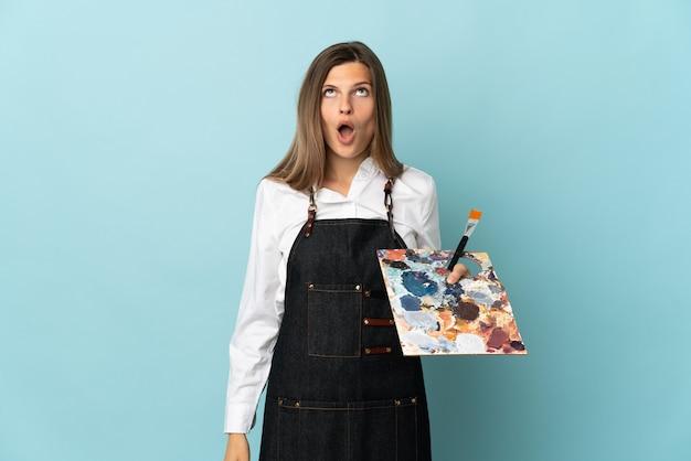 Jovem artista eslovaca isolada em um fundo azul, olhando para cima e com expressão de surpresa