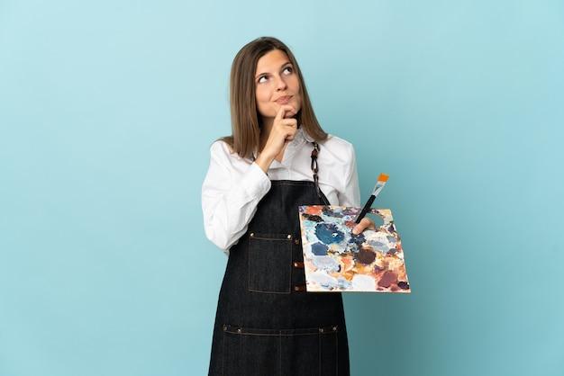 Jovem artista eslovaca isolada em um fundo azul olhando para cima