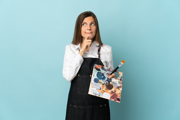 Jovem artista eslovaca isolada em um fundo azul, tendo dúvidas e pensando.