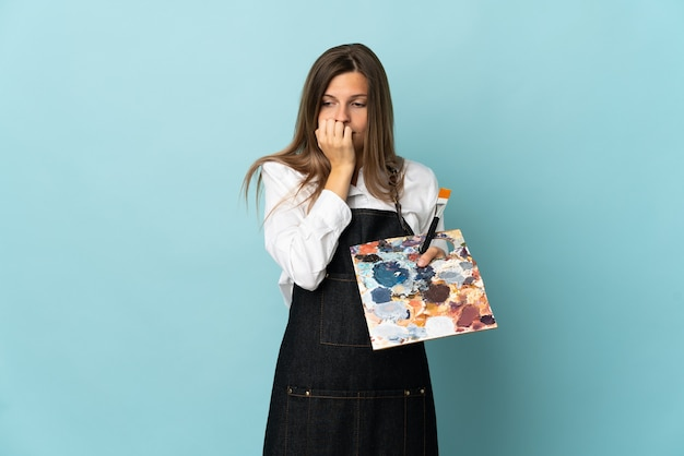 Jovem artista eslovaca isolada num fundo azul com dúvidas