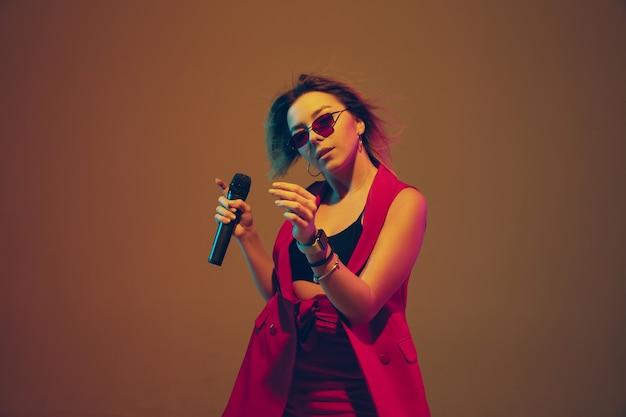 Jovem artista feminina, caucasiana, cantando, dançando em luz de néon em fundo gradiente