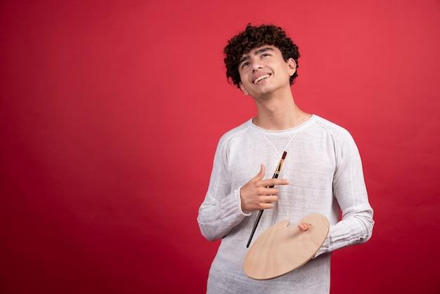 Jovem artista masculino com paleta e pincéis sorrindo.