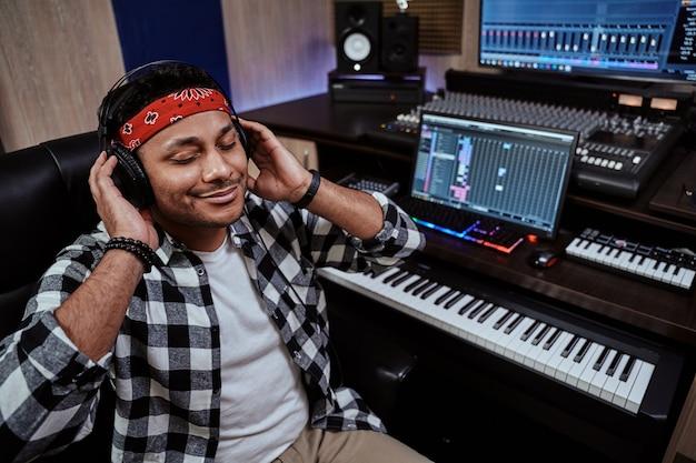 Jovem artista masculino em fones de ouvido sentado com os olhos fechados enquanto ouve música na gravação