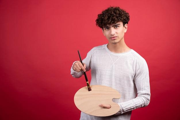 Jovem artista masculino olhando para a câmera com ferramentas de pintura.