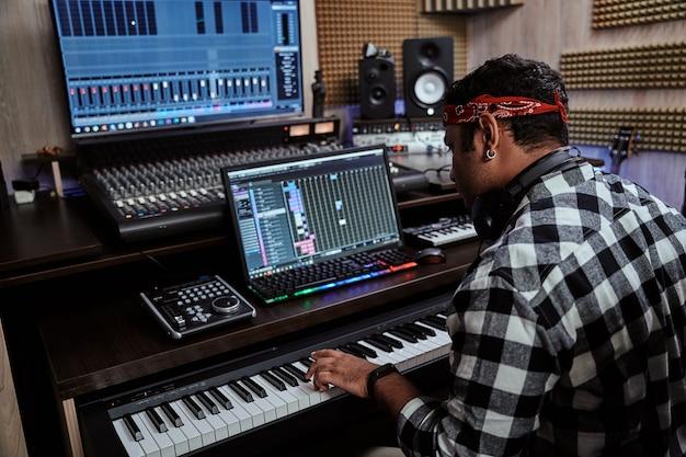 Jovem artista masculino parecendo focado enquanto toca o teclado sintetizador sentado na gravação