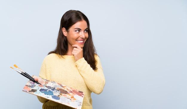 Jovem artista mulher azul pensando uma idéia e olhando de lado