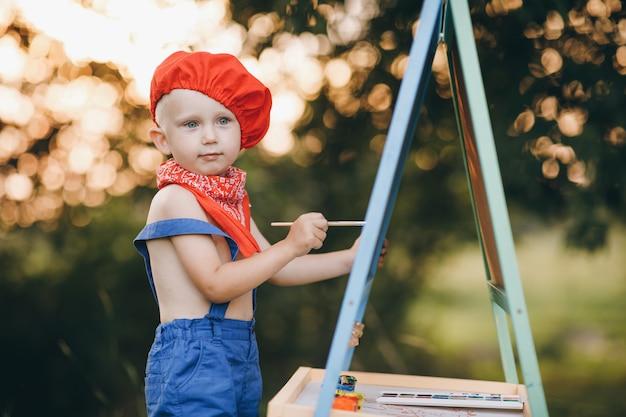 Jovem artista pintando uma paisagem de verão. menino pintor sobre a natureza do artista desenha