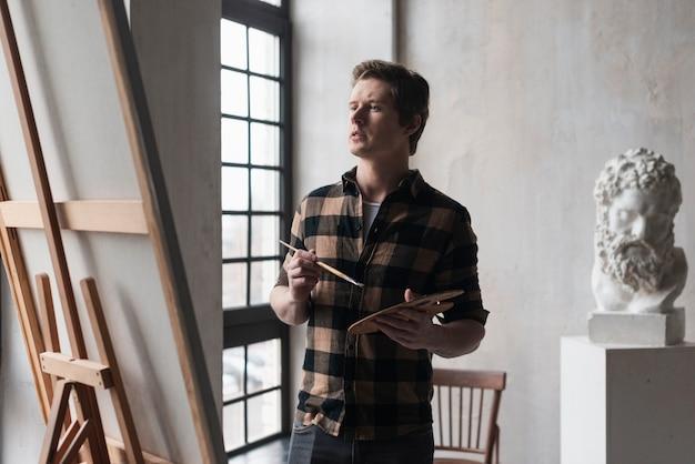 Jovem artista procurando detalhes em pintura