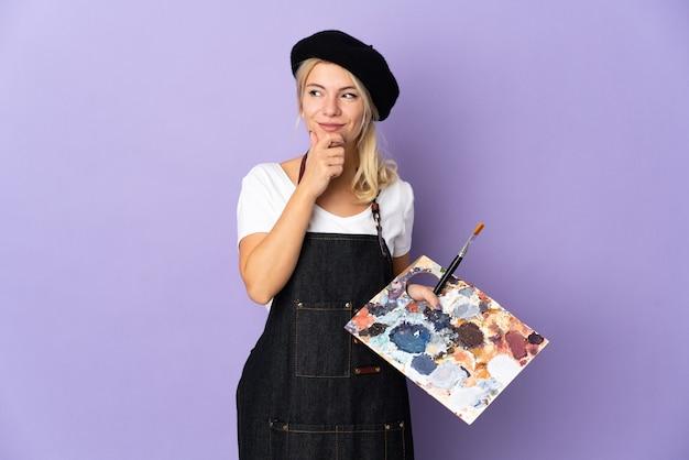 Jovem artista russa segurando uma paleta isolada em um fundo roxo e olhando para cima