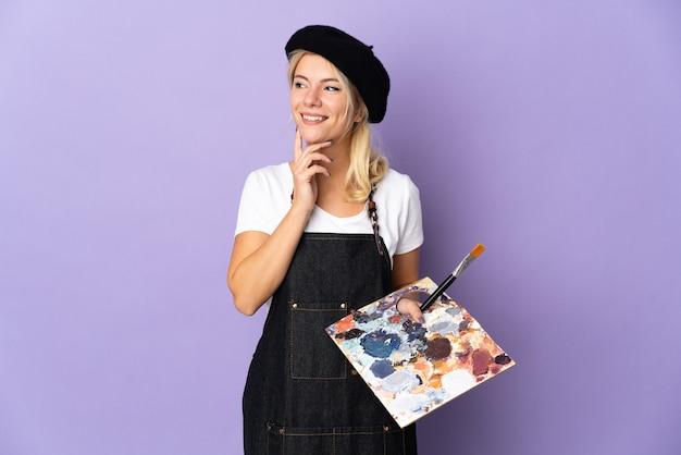 Jovem artista russa segurando uma paleta isolada em um fundo roxo pensando uma ideia enquanto olha para cima
