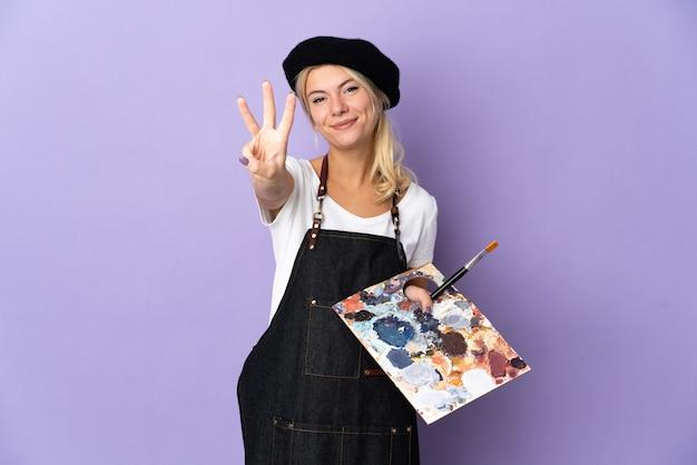 Jovem artista russa segurando uma paleta isolada no fundo roxo feliz e contando três com os dedos