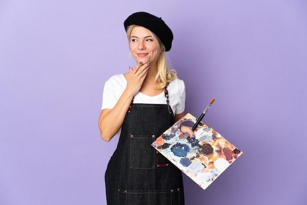 Jovem artista russa segurando uma paleta isolada no fundo roxo, olhando para cima enquanto sorri