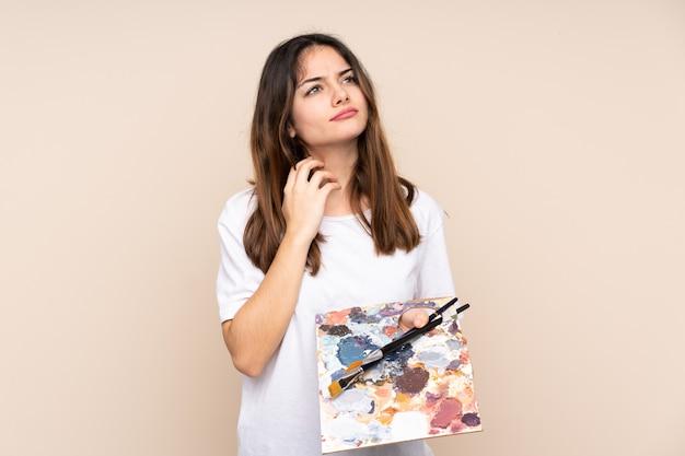 Jovem artista segurando uma paleta i