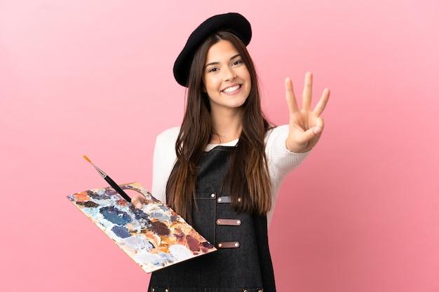 Jovem artista segurando uma paleta sobre um fundo rosa isolado feliz e contando três com os dedos