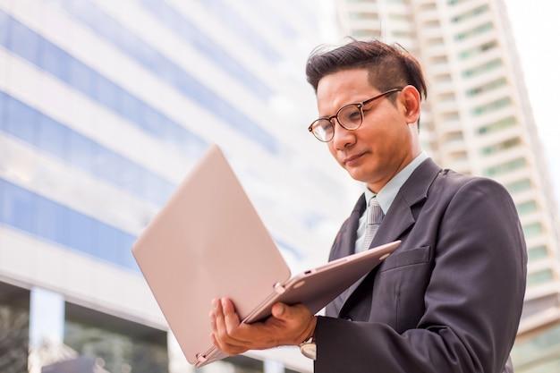Jovem, ásia, homem negócios, em, paleto, com, seu, computador laptop, ao ar livre, modernos, predios, experiência