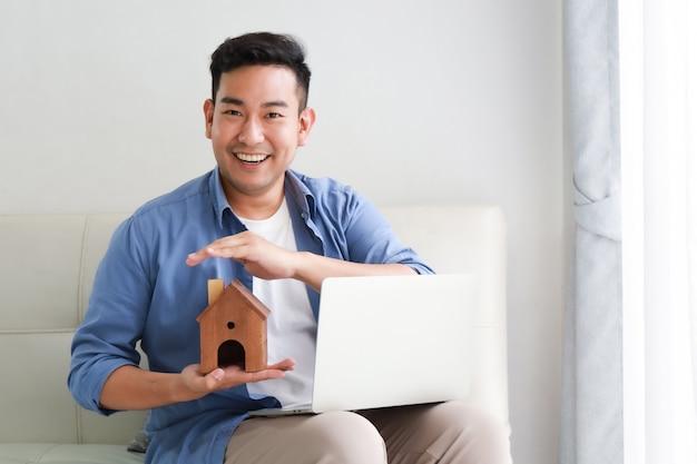 Jovem, asian tripulam, em, camisa azul, com, computador laptop, e, pequeno, casa, modelo, mostrando, para, empréstimo banco, para, casa, conceito, em, sala de estar