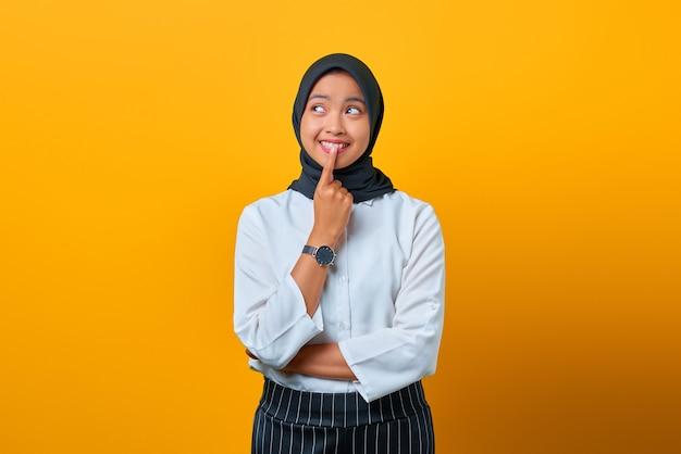 Jovem asiática animada tocando os lábios e tendo ideias sobre fundo amarelo