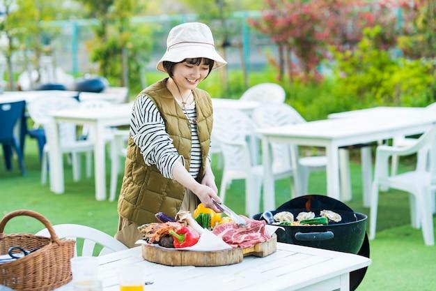 Jovem asiática assando ingredientes no churrasco