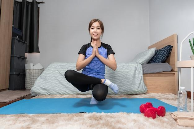 Jovem asiática atraente e saudável fazendo exercícios em casa